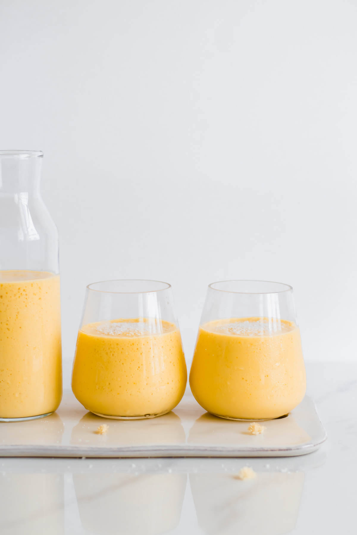 mango lassi in glasses topped with coconut flakes