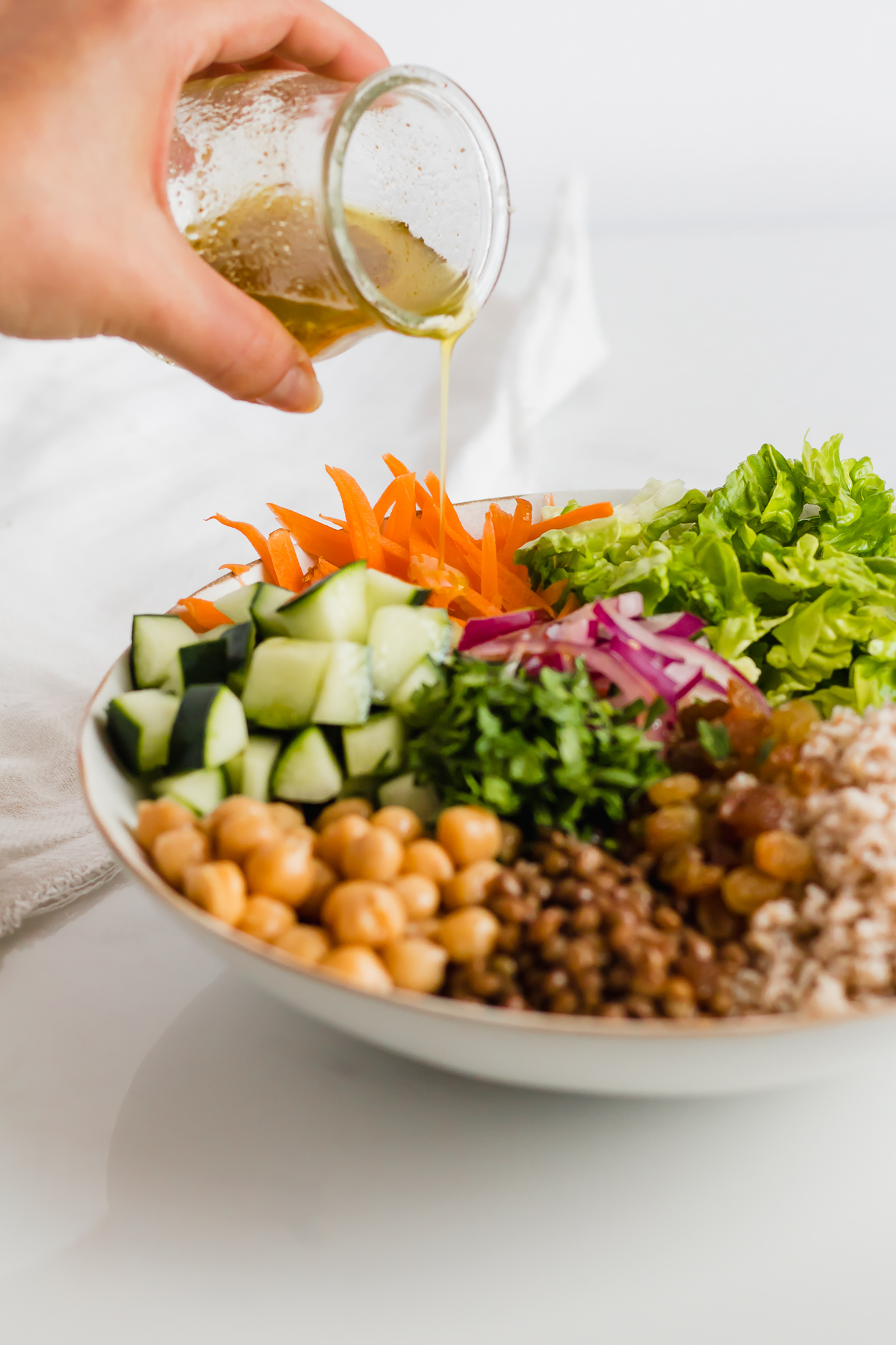 dressing poured over moroccan couscous salad with chickpeas